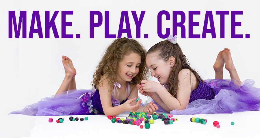 Make. Play. Create. Girls playing with beads on floor.